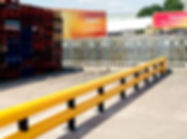 crash barrier yellow sunny day ouside a warehouse