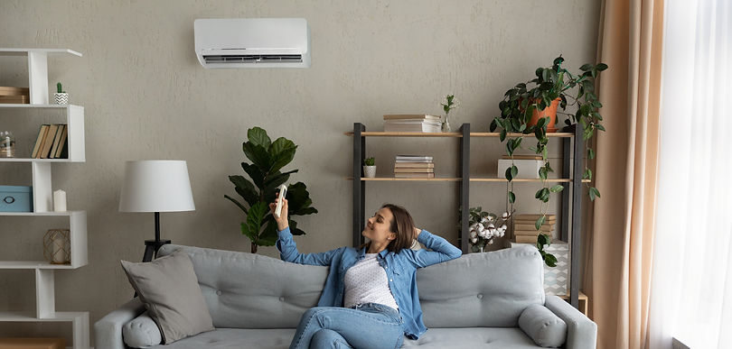 Happy young Caucasian woman relax on couch in living room turn on air conditioner with rem
