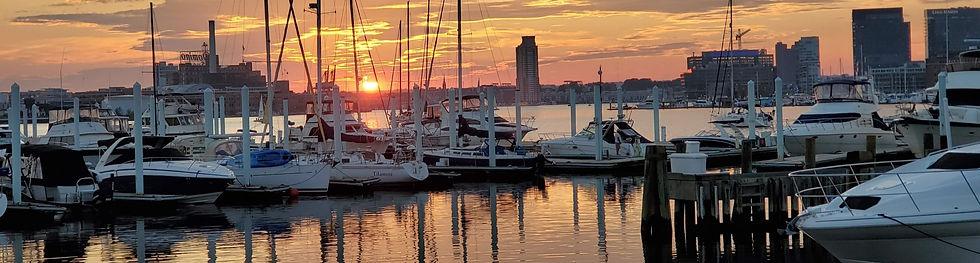 Baltimore waterfront, sunset, and sailboats.