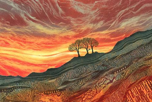 Blaze of Glory sunset sky with trees on a rocky hillside. Rebecca Vincent prints