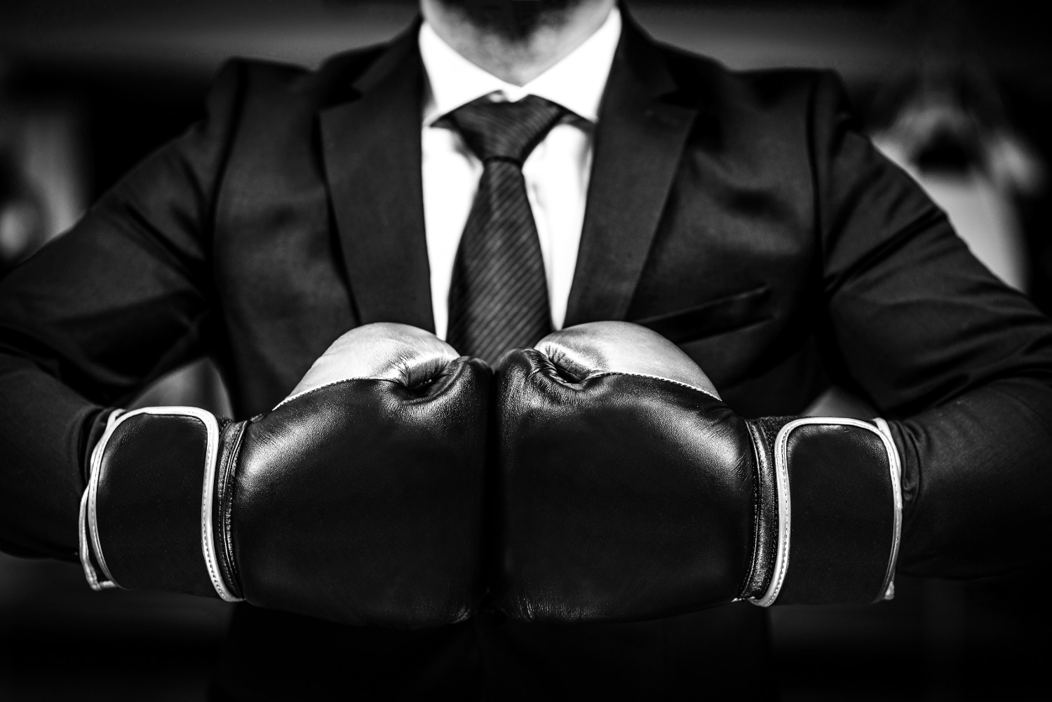 Businessman with boxing gloves is ready for corporate battle. Man in suit, shirt and a tie is holdin