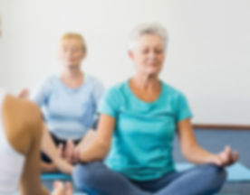 Instructor performing yoga with seniors during sports class.jpg
