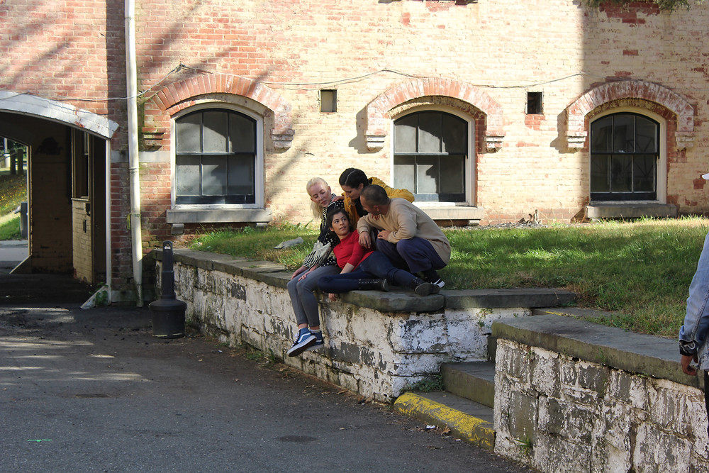 On the edge of a rock wall, with a grassy hill a pile up of dancers, dressed in evvery day clothing, look at one another, playfully waiting for their next move.