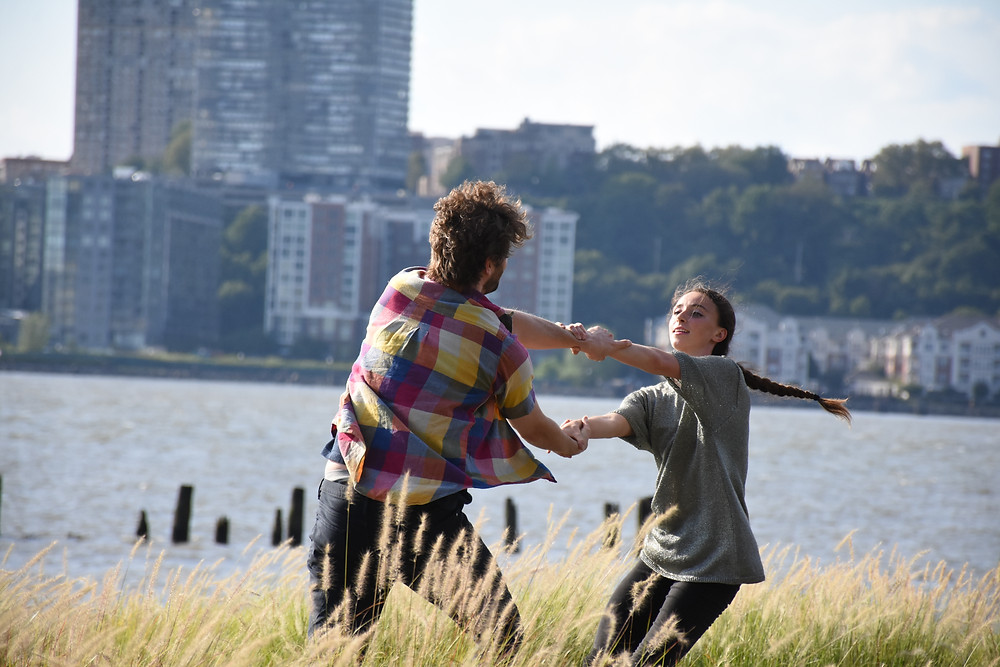 Andrew, a tall male dancer in a plaid button down that is flowing in the breeze, swings hand to hand with Therese, tiny with a long braind flying behind her, the two are holding one another at the wrists, right arm over left arm, weight back, trusting one another to keep holding on.