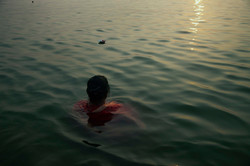 A woman immersing herself on the Ganges River during sunrise, the most important time of the day in