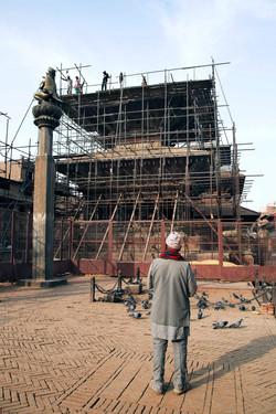 A man watching the reparation of Vishwanath Temple