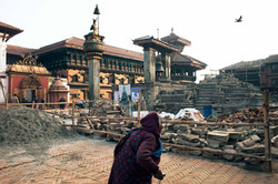 A local passing the destroyed Vatsala Durga Temple in Bhaktapur