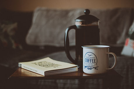 closed-book-beside-french-press-and-mug-