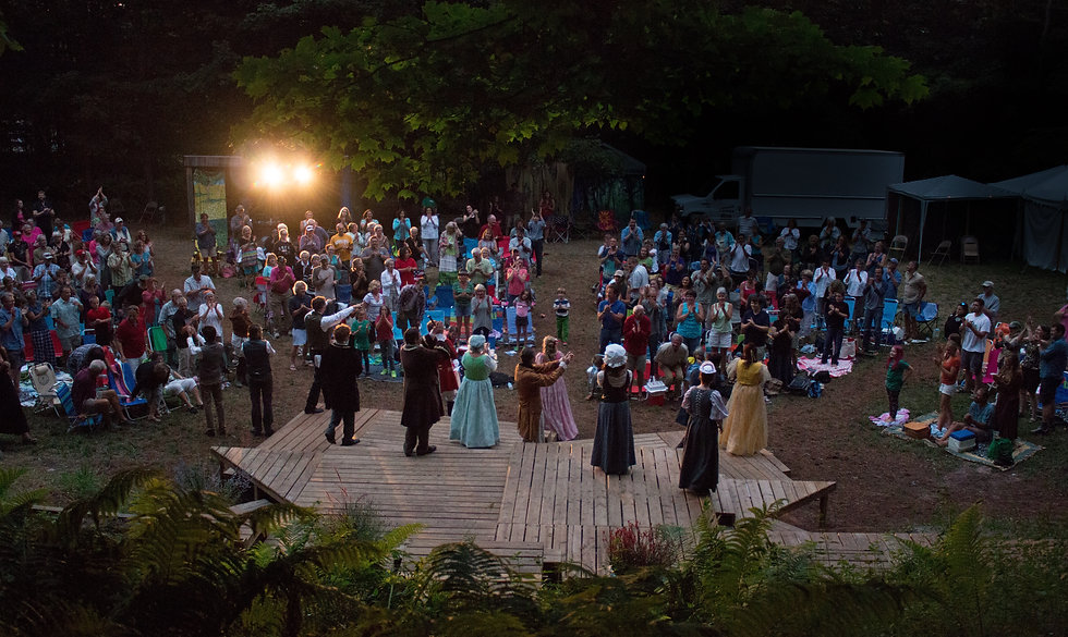 Audience at outdoor theater applauds Shakespeare troupe. Actors face the audience, pointing and clapping. It is dark, and the stage lights shine brightly into the camera.