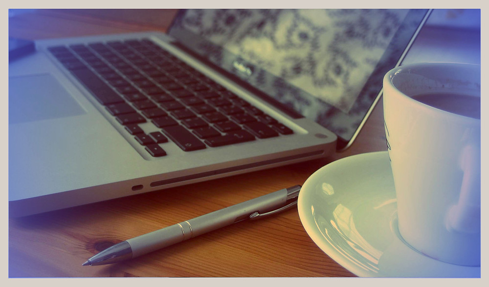 A photo of a laptop, coffee mug, and pen on a desk