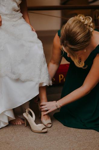 A bridesmaid helps a bride into wedding shoes