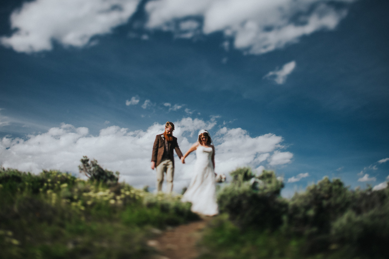 A bride and groom hold hands and walk across a hilltop in Crested Butte Colorado