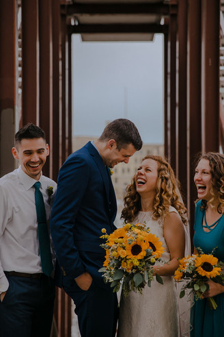 A wedding party laughs at each other in a Kadish Park wedding