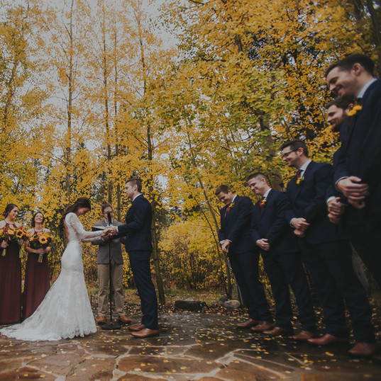A bride, groom, and wedding party celebrate during a wedding ceremony at Quaking Aspen Amphitheatre Warren Station at Keystone wedding