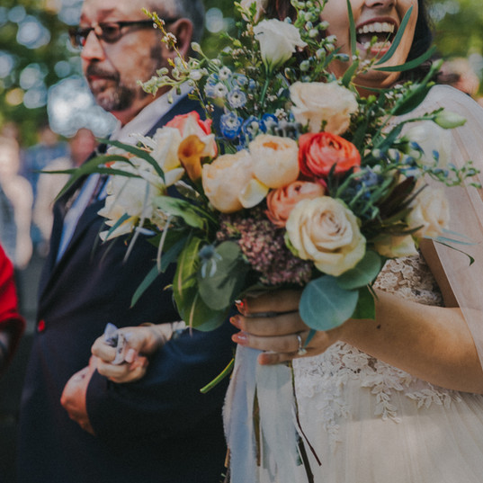 A close up of a bride's bouquet  as her dad walks her down the aisle in a Wildcat Mountain State Park wedding