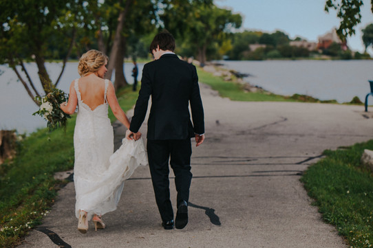 A bride and groom walk along a paved pathway during Asylum Point Oshkosh wedding photos