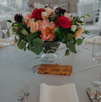 A centerpiece of roses and mixed florals at The Manor House Wedding