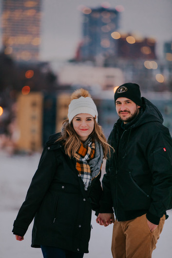 A man and woman smile at in front of the Milwaukee skyline during Kadish Park engagement photos