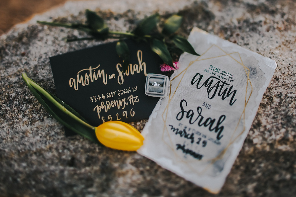 A wedding invitation suite and a diamond ring in a velvet ring box sit on top of a large rock in Racine Wisconsin