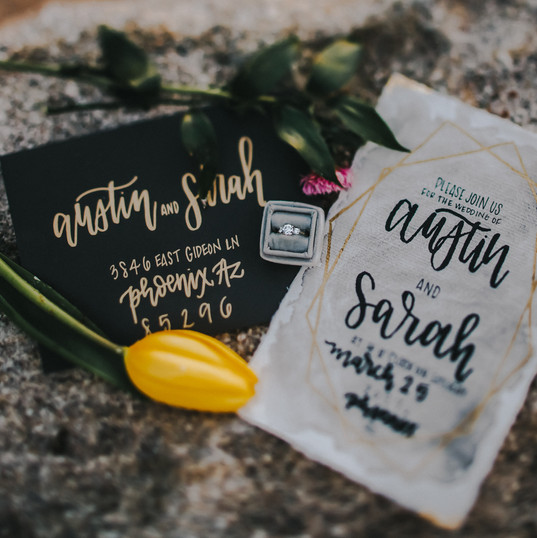 A wedding invitation and envelope with custom calligraphy lay on top of a rock in a Madison Wisconsin wedding