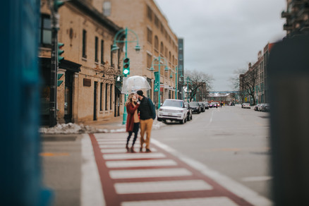 A man and woman kiss as they walk on the crosswalk in the city