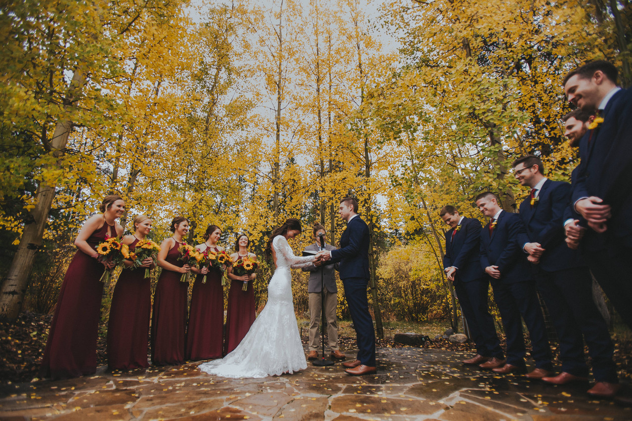 A bride and groom recite their vows to each other in front of fall folleage in the Quaking Aspen Amphitheater at Keystone Resort
