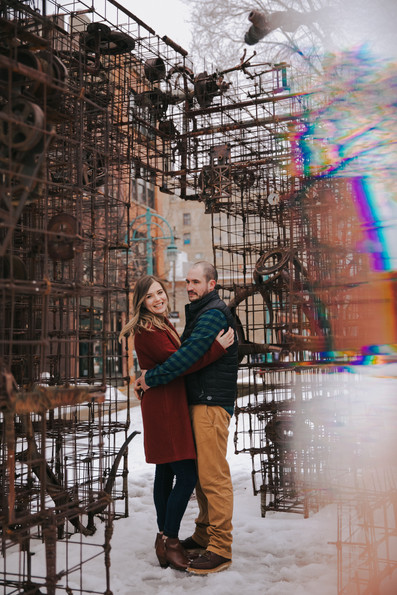 A man and woman stand near a steel sculpture on Catalano Square