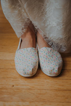 A close up of a bride's TOMS brand shoes in Milwaukee, Wisconsin