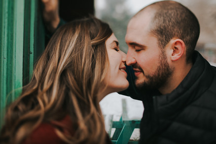 A man and woman lean in for a kiss during Catalano Square engagement photos