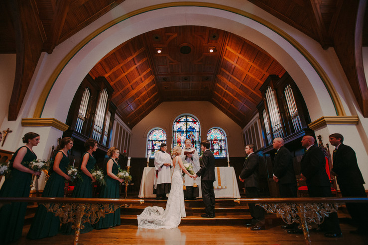 A bride, groom, and wedding party stand near an alter during a wedding ceremony