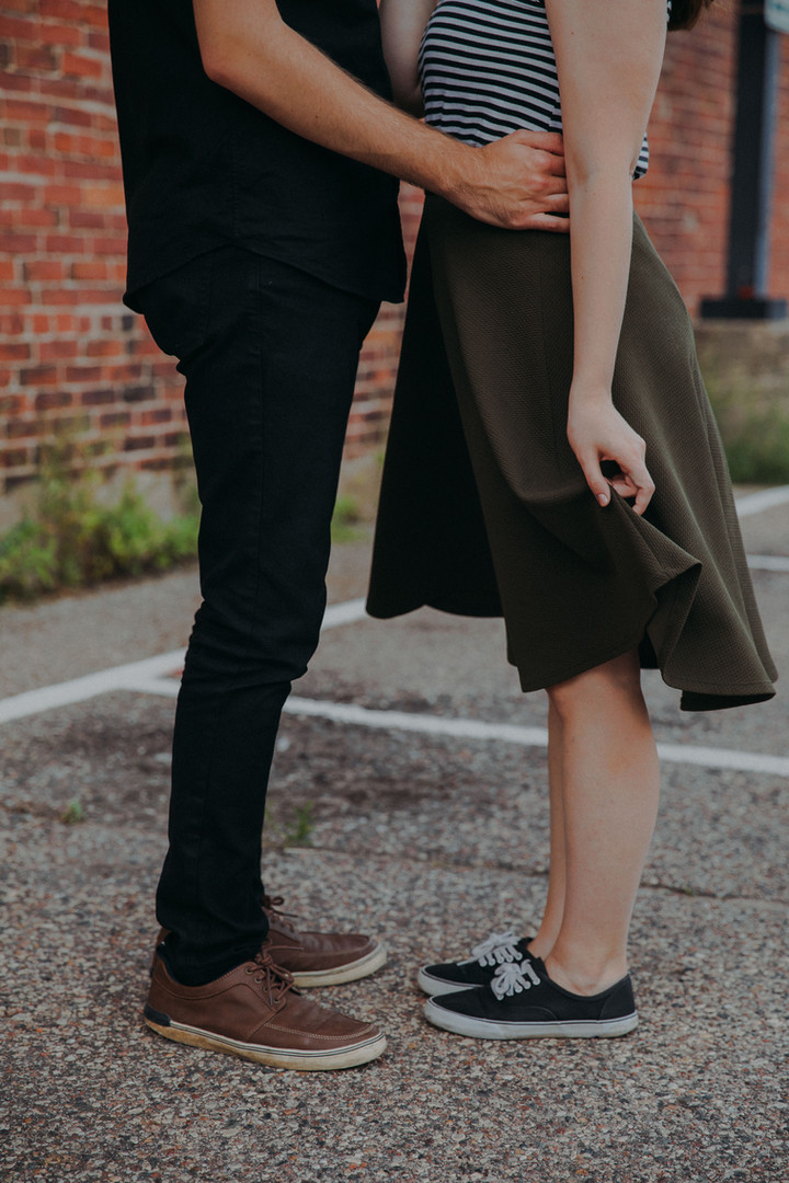 A waist down close up of a man with his hands on a woman's hips in a Historic Downtown Stevens Point engagement session