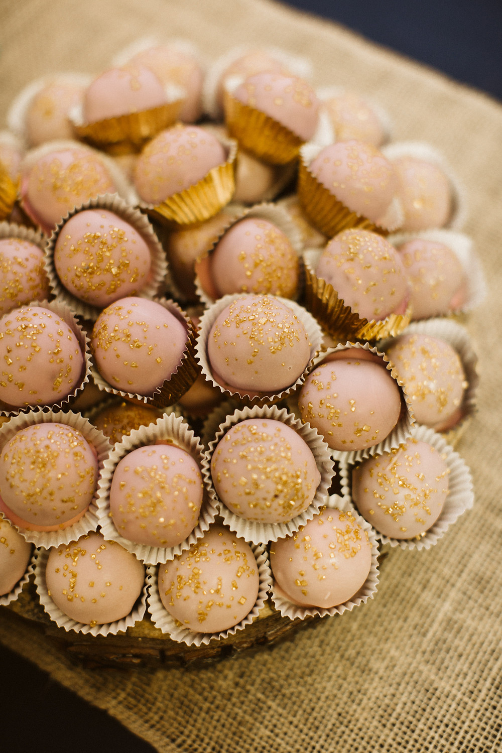 A close up of cake bites dusted in gold powder from Hailey's Sweets and Treats in a Wisconsin wedding
