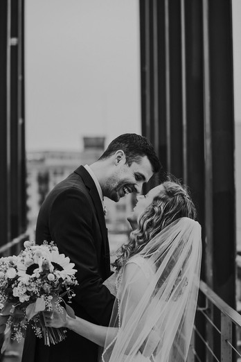 A bride and groom laugh at each other on the bridge at Kadish Park