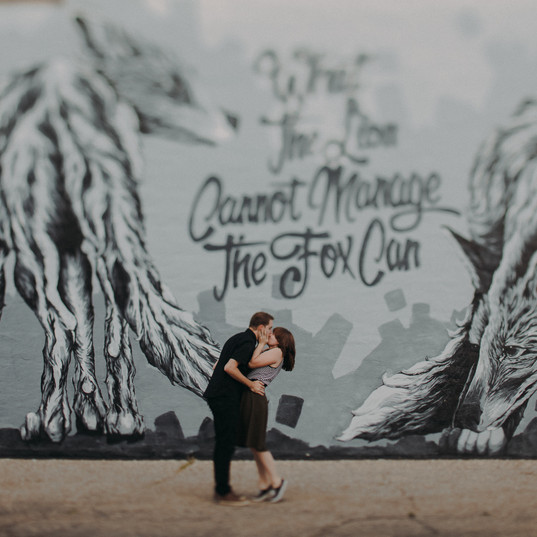 A man and woman kiss in front of Alexander Landerman's Mural in Downtown Stevens Point