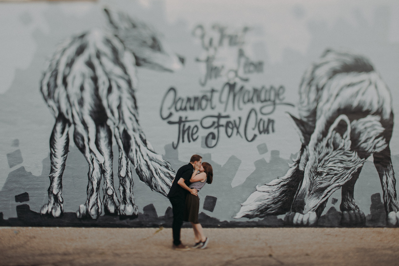 """A man and woman kiss in front of Alexander Landerman's mural """"What the Lion Cannot Manage the Fox Can"""", in a Historic Downtown Stevens Point engagement session"""