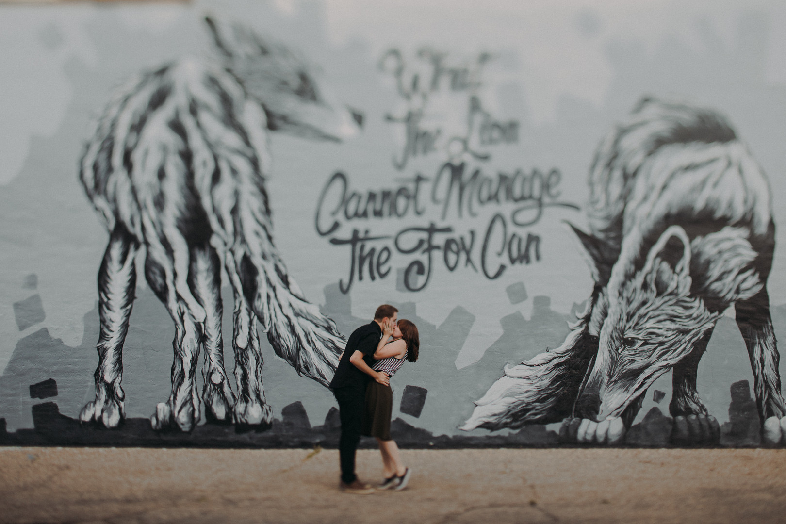"A man and woman kiss in front of Alexander Landerman's mural ""What the Lion Cannot Manage the Fox Can"", in a Historic Downtown Stevens Point engagement session"