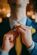 A groom straightens his tie at the Red Lion Pub Milwaukee