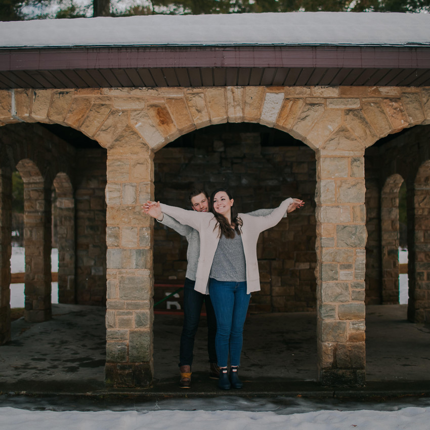 A man and woman stand in a historic building at a park during Wisconsin engagement photos