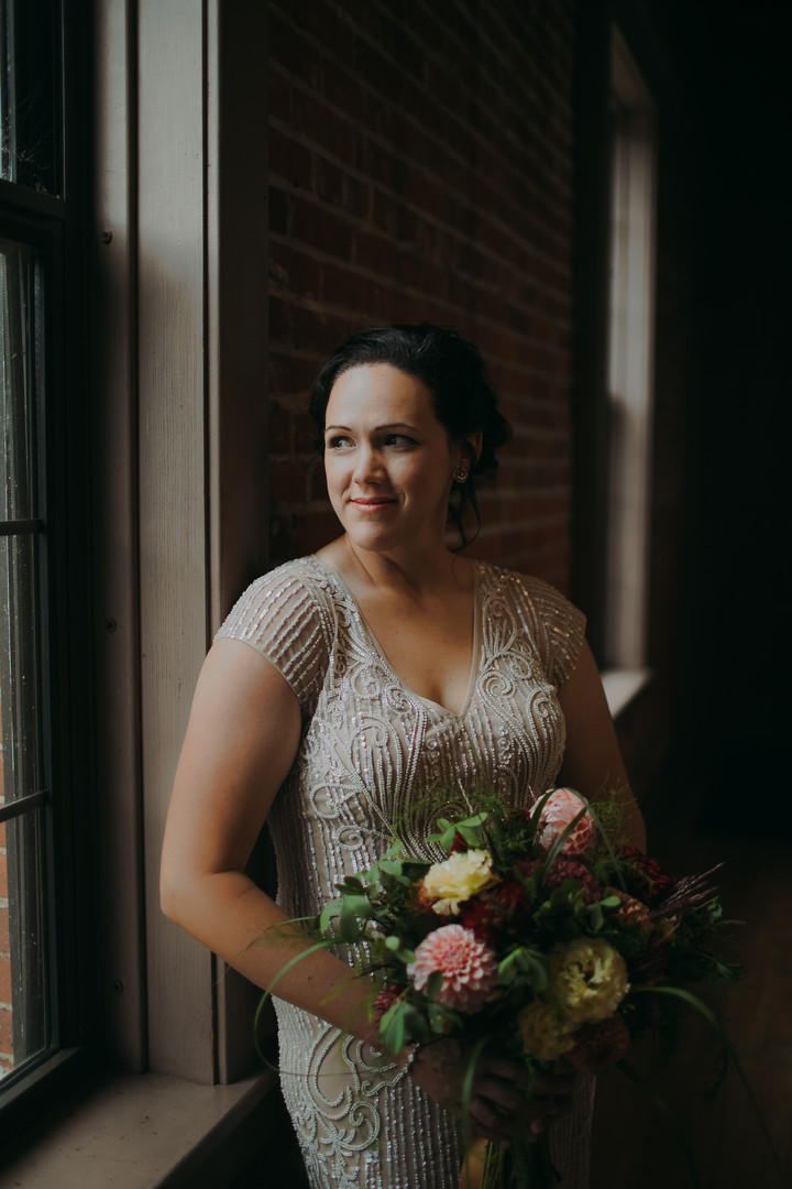 A portrait of a bride looking outside the window at a Pfiffner Building wedding in Downtown Stevens Point Wisconsin