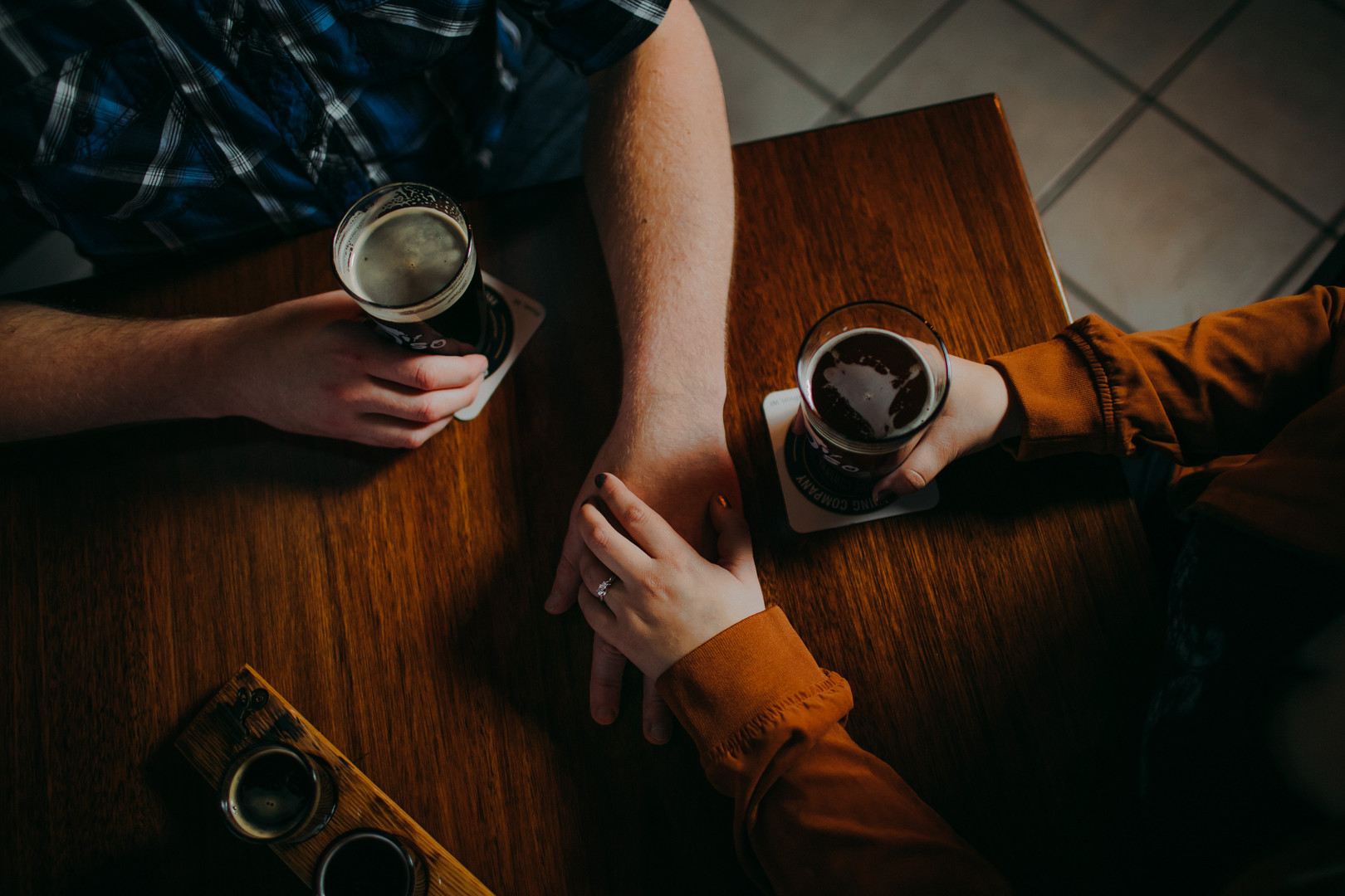 A close up of a man and woman holding hands and drinking beer at an O'so Brewing Company engagement session in Plover Wisconsin