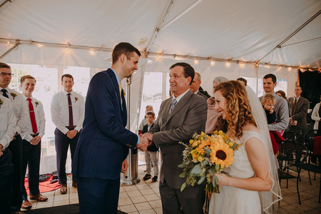 A man shakes the hand of the father of a the bride during a Milwaukee wedding ceremony