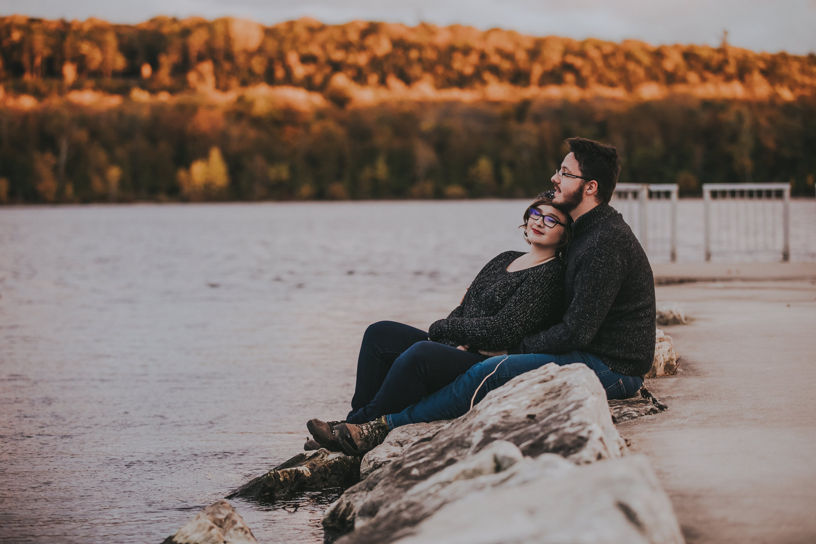 A man and woman rest on the side of Nicolet Bay Boat Launch at a Penninsula State Park engagement session
