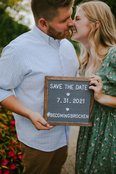 A man and woman hold up a changeable letter sign for their save the date