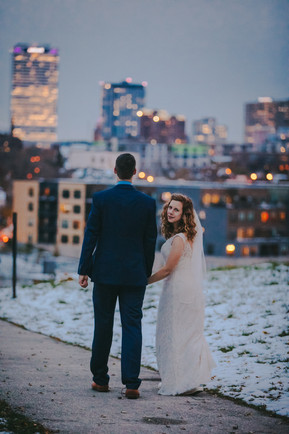 A bride looks over her should at the camera near the Milwaukee Skyline