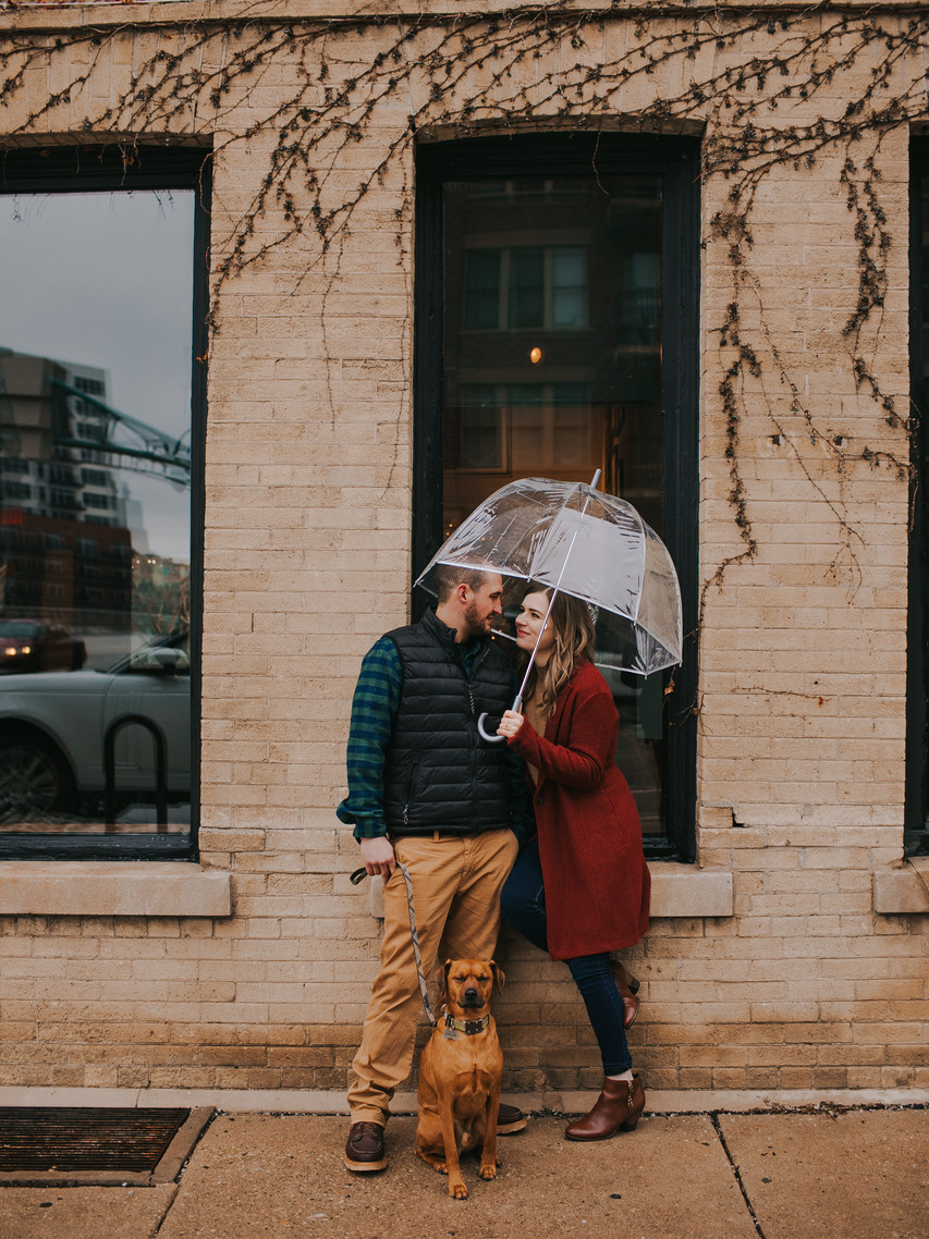A man, woman, and dog pose under an umbrella during Historic Third Ward engagement photos