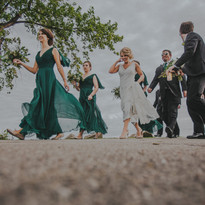 A bridal party walks along the river in downtown Oshkosh