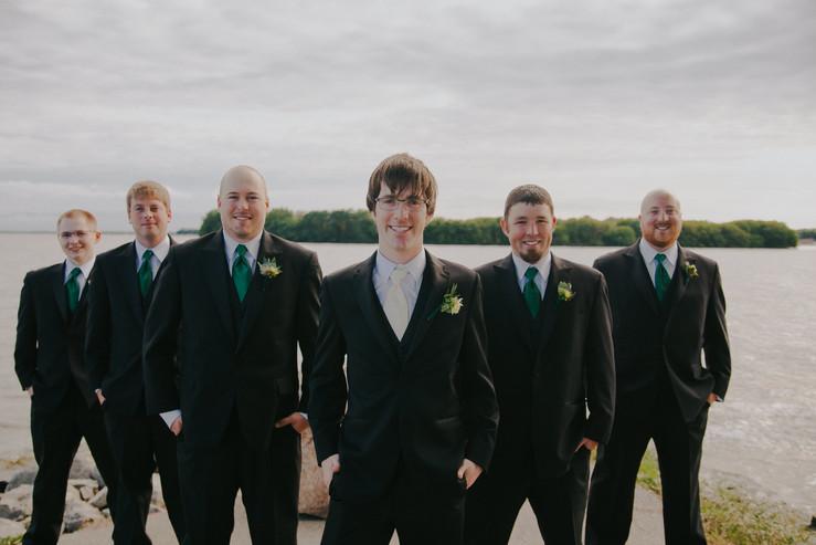 Groomsmen pose for photos along the Fox River