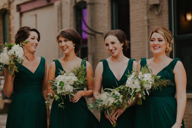 Bridesmaids smile and laugh in Downtown Oshkosh wedding photos