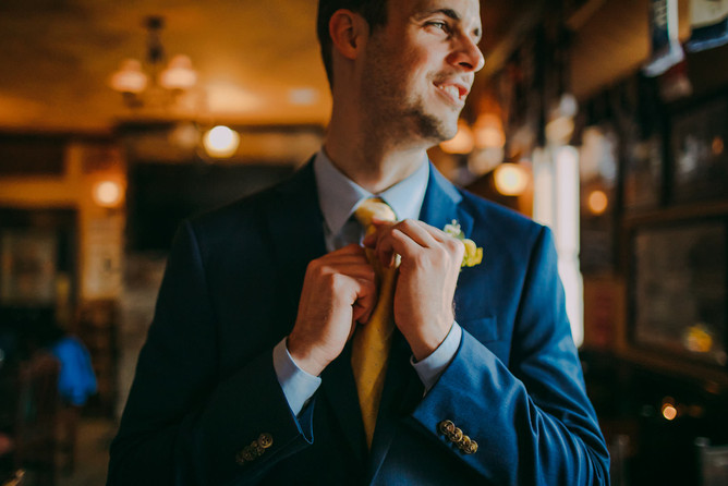 A groom straightens his tie while looking out a window at downtown Milwaukee