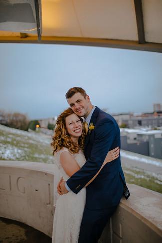 A bride and groom hug and smile at the camera at Kadish Park